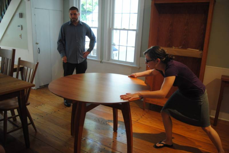 Liz from Sales at Vermont Woods Studios inspects a new table