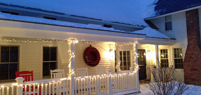 The front porch of Stonehurst is decorated with a wreath which doubles as a snow sled