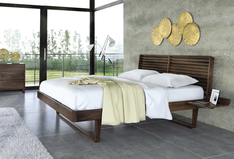 The Contour bed in natural walnut wood looks lovely beneath brass wall hangings.