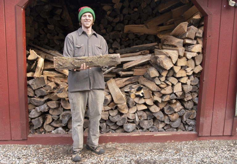 Jake Checani, land steward at VWS, stands in front of shed filled with firewood