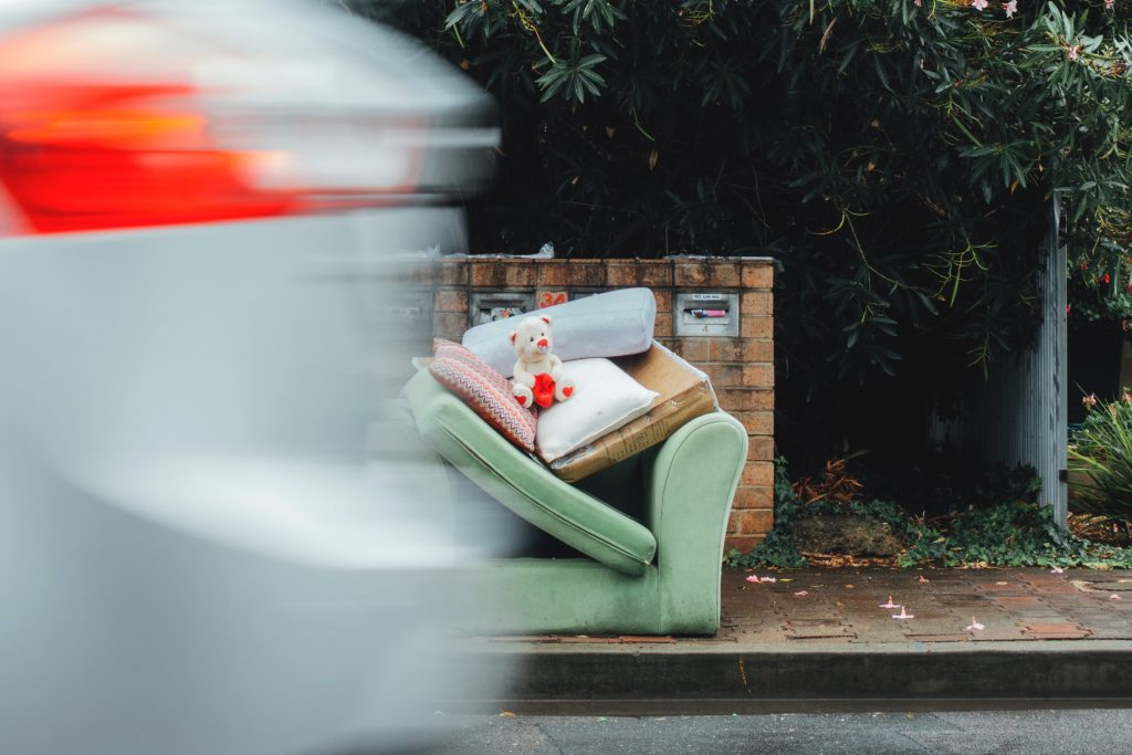 A Green sofa left on a curbside for disposal